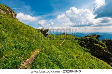 Path To The Edge Of A Hill. Beautiful Mountainous Landscape With Grassy Hillside And Giant Boulders