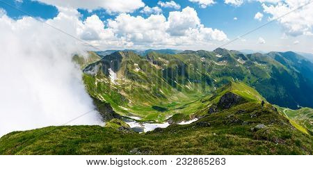 Mountainous Panorama With Rising Clouds. Beautiful Landscape With Some Snow On Grassy Hillsides. Pop