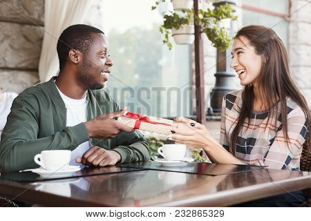 Young African-american Man With Giftbox Surprising His Girlfriend With Anniversary Present, Sitting