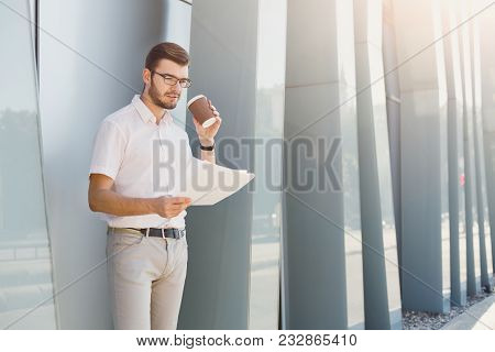 Attractive Thoughtful Businessman Or Lawyer In Eyeglasses Is Checking Contract Documents While Stand