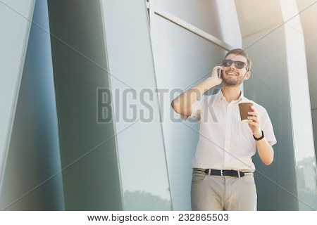 Attractive Smiling Businessman In Sunglasses Is Talking On Cell Phone And Drinking Coffee While Stan