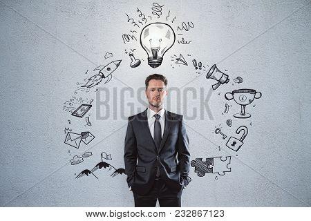 Presentation And Solution Concept. Portrait Of Handsome European Businessman Standing On Concrete Wa
