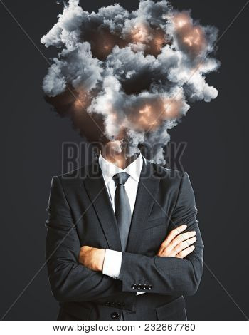 Businessman With Abstract Explosion Smoke And Fire Head Standing On Dark Background. Disaster And St
