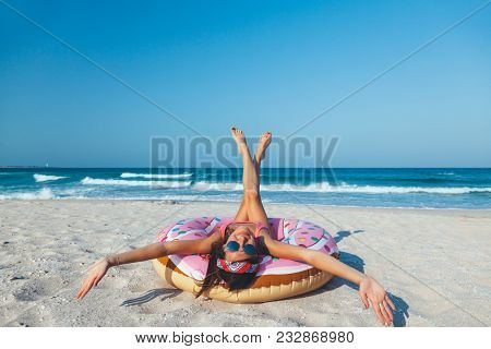 Girl relaxing with donut lilo on the beach. Playing with inflatable ring. Summer holiday idyllic on a tropical island.