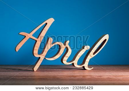 April - 2nd Month Of Spring. Wooden Carved Word At Dark Blue Background. Card For Fools Day, 1st Apr