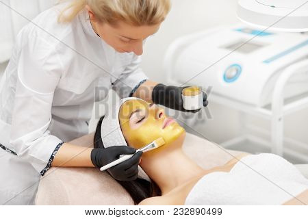 Applying Of Gold Facial Mask In Beauty Salon. Cosmetologist Using Brush For Procedures. Anti Wrinkle