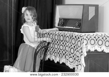 Beautiful Little Girl With Interest Looking At An Old Tube Radio. This Receiver She Sees For The Fir