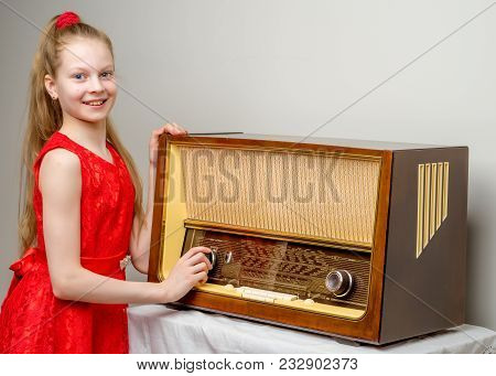 Beautiful Little Girl On An Old Radio. The Concept Of Old Things, Nostalgia, Vintage.