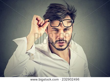 Young Man In Formal Shirt Taking Off Eyeglasses Looking At Camera With Doubts.