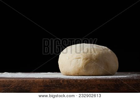 Pizza Dough Or Baking On A Dark Black Background Of Wood. Baking Bread, Pizza, Pasta. Recipe From Ch