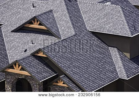 Rooftop in a newly constructed subdivision in Kelowna British Columbia Canada showing asphalt shingles and multiple roof lines poster