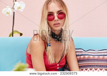 Fashionable Woman With Serious Expression Wears Stylsih Shades, Casual Clothing, Sits On Comfortable