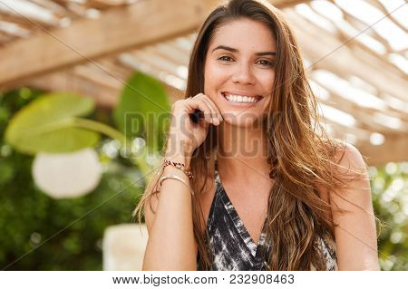 Brunette Smiling Female Sits In Outdoor Cafeteria, Has Broad Smile, Has Good Rest, Has Satisfied Exp