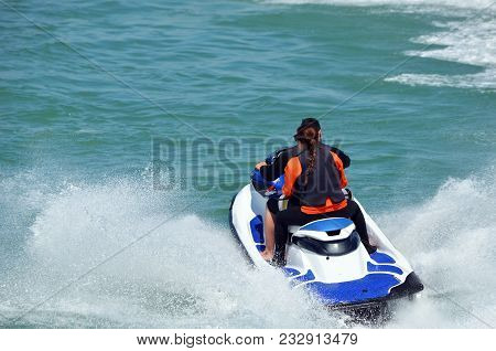 Young Couple Riding Tandem On A Blue And White Jet Ski.