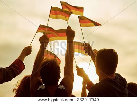 People Hold German Flags. Silhouette Of Patriotic Deutsch Crowd, Rear View. Gloving Evening Sun Back
