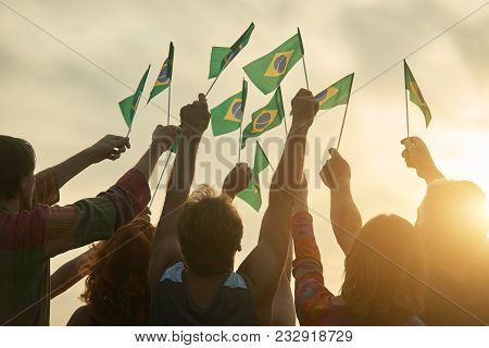 Rising Up Brazil Flags. Crowd Of People Holding Brazilian Flags, Back View.