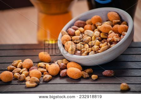 Tasty Salty Mix Of Nuts In Bowl And On Wooden Table.