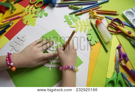 Small Child Makes Paper Crafts For Mother`s Day Or Birthday. Small Child Doing Paper Flowers For Mom