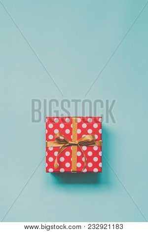 Top View Of A Red Dotted Gift Box Tied With Golden Bow Over Blue Background. Vintage Effect. Copy Sp