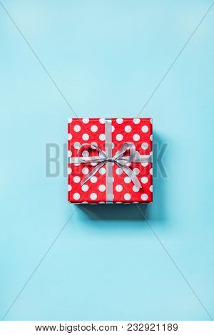 Top View Of A Red Dotted Gift Box Tied With Golden Bow Over Blue Background.