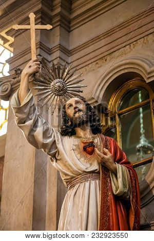 Lisbon, Portugal - October 24, 2016: Jesus Christ statue holding Cross or Crucifix and Sacred Heart on chest. Santo Antonio de Lisboa Church. Saint Anthony of Lisbon (Padua or Padova) church