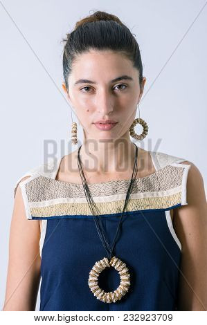 Close Up Of A Beautiful Woman Portrait With Rounded Necklace And Earrings