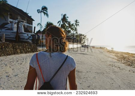 View From Back Young Woman With Backpack Walking Along Ocean Shoreline At Sunset