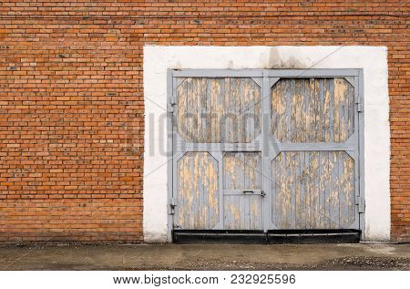 Gray Large Garage Door Brick With A Lock On The Door