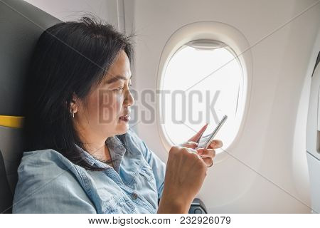 Asian Woman Sitting At Window Seat In Airplane And Turn On Airplane Mode On Mobile Phone Before Take