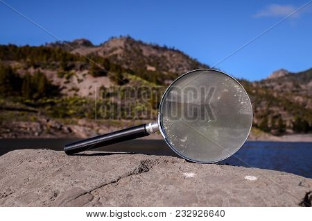 Investigation Concept Magnify Glass Loupe On The Volcanic Rock Near A Lake