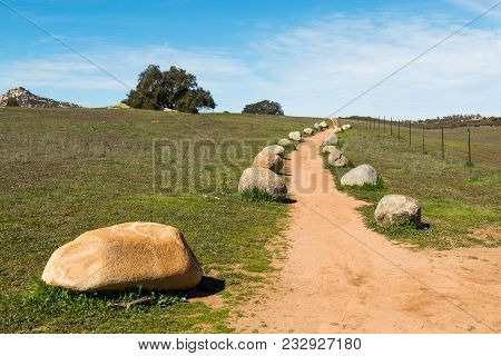 A Dirt Trail Leading Up To A Hilltop Lined With Boulders At Ramona Grasslands Preserve In San Diego,