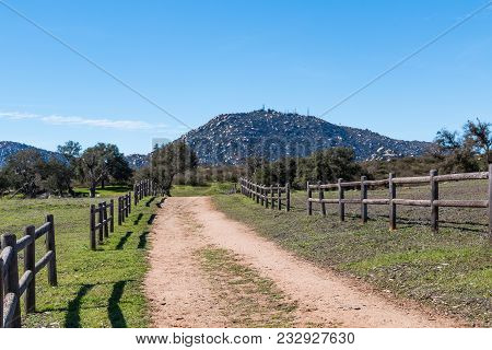 A Dirt Road Lined With A Wooden Fence Leading To Mount Woodson At Ramona Grasslands Preserve In San
