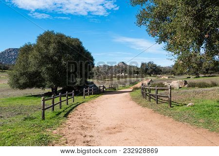 A Dirt Road Lined By Wooden Fencing At Ramona Grasslands Preserve In San Diego, California.