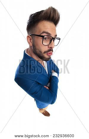smart casual man with arms folded is caught off guard by something on the side, making a surprised face while standing on white background, full body shot