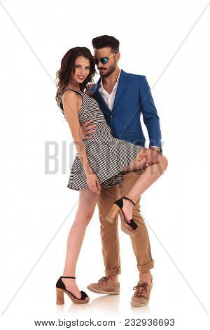 sexy man holding hand on his woman's thigh and looking seductively at her while she leans on him, on white background