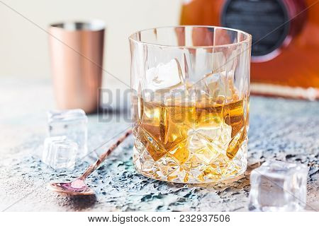 Glass Of Scotch Whiskey With Ice Cubes, Bottle And Copper Bar Accessories