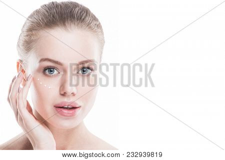 Beautiful woman with perfect skin applying cream, isolated on white background