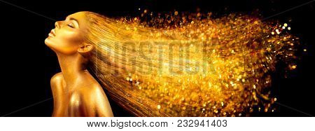 High Fashion model woman in golden bright sparkles. Art Gold skin girl face portrait closeup. Beauty gold eyes, Lips, Skin and  dyed hair. Lady with holiday Glamour shiny professional makeup on black poster