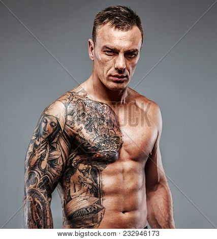 Muscular Tattooed Fighter Against Grey Background. Studio Shot