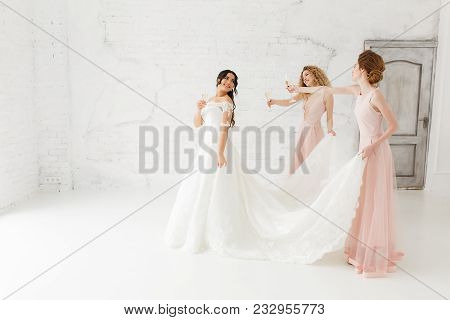 Happy Beautiful Bride And Bridesmaid Adjusting Her Wedding Dress. Drinking Champagne.