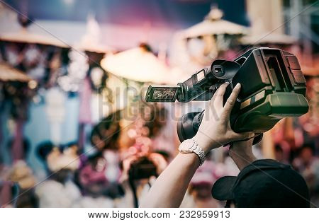 Video camera operator working with his equipment. Cameraman lifts the camcorder above his head while filming video with colorful light poster