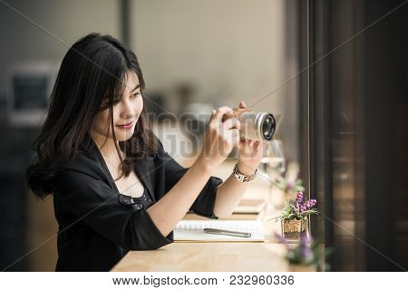 Beautiful Woman In Black Suite Holding Camera ,looking At Screen And Taking Photos While Working At
