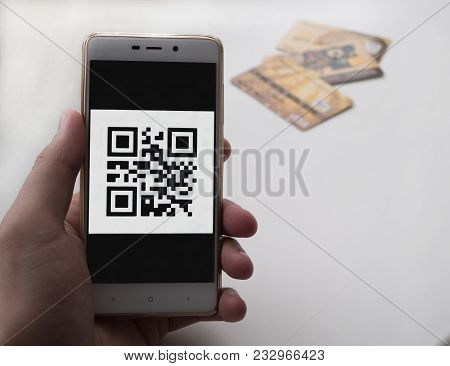 Man Hand Holding A Phone With Qr Code On The Screen. There Are 3 Bank Cards On The Background