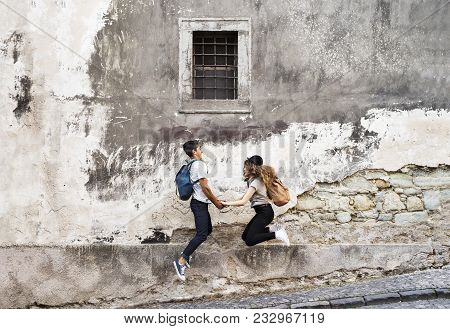 Two Beautiful Young Tourists In The Old Town Having Fun. Teenagers Jumping Against An Old Wall.