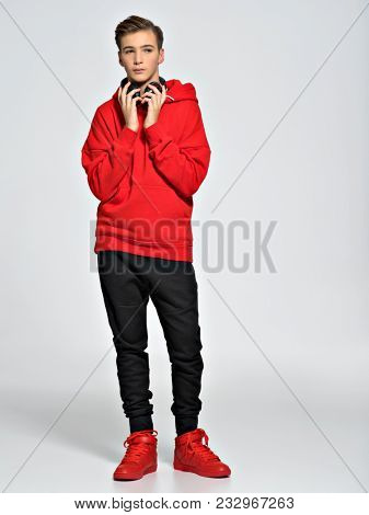 Handsome teenage boy with headphones. Young teenager dressed with fashionable clothes - posing on white background