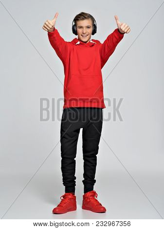 Teenage boy dressed in a red hoodie and street sneakers. Teenager wears fashionable fall clothes and shows thumbs up - posing over white background. Full portrait.