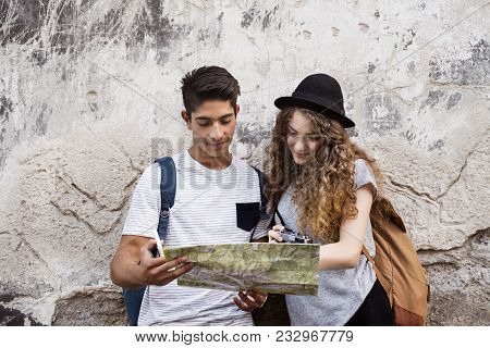 Two Beautiful Young Tourists In The Old Town. Teenagers With A Map And A Camera Leaning Against Old