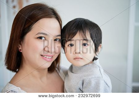 Head And Shoulders Portrait Of Beautiful Asian Woman Looking At Camera With Wide Smile While Holding
