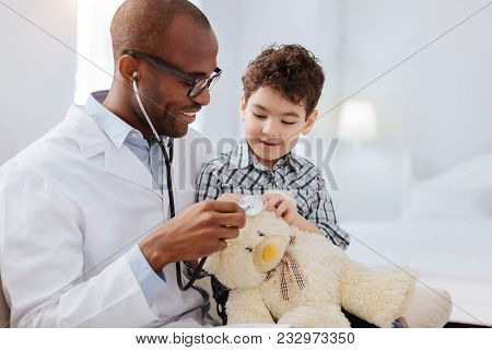 Doctor For Toy. Merry Glad Male Doctor Posing With Boy On Light Background While Examining Plush Bea