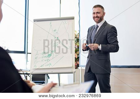 Portrait Of Bearded Business Coach Smiling Cheerfully While Standing By Whiteboard Giving Presentati